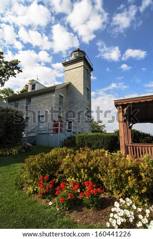 The Sodus Point Lighthouse in New York sits along the southern shore of Lake Ontario at Sodus Bay. - stock photo