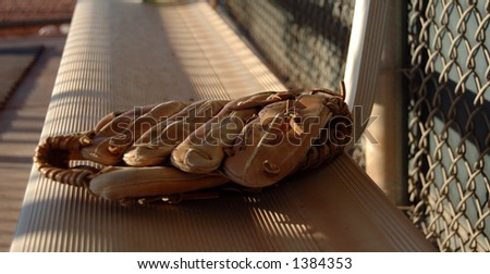 The soft glow of sunset falls on a baseball glove left on the bench after the game. - stock photo