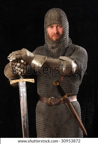 The soldier in a medieval knightly armour with we throw in hands - stock photo