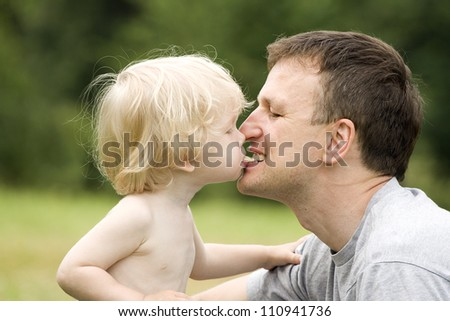 The son feeds the father with bread - stock photo