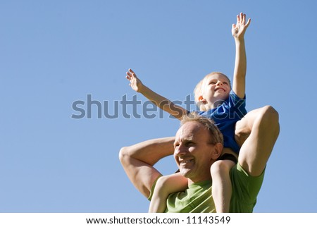 The son on shoulders at the father against the sky