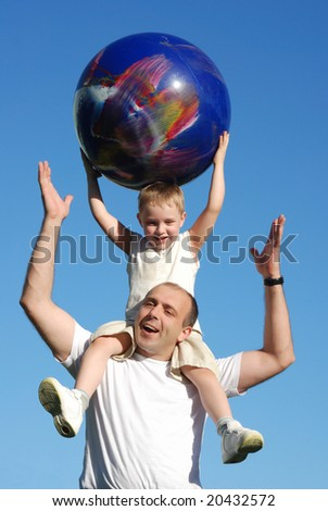 The son on shoulders at the father against the sky - stock photo