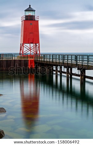The South Pier Lighthouse at Charlevoix, Michigan is reflected on the water with a colorful, cloudy sky.