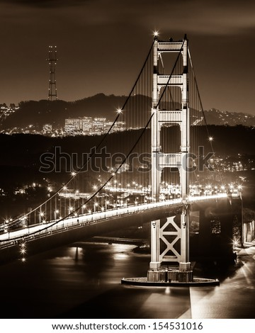 The South tower of Golden Gate Bridge at night in black and white. - stock photo