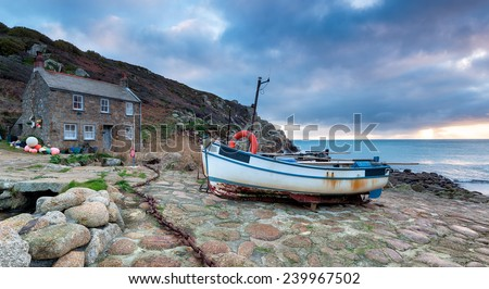 The South West Coast Path as it passes through fishing boats and cottages at Penberth Cove near Penzance in Cornwall - stock photo