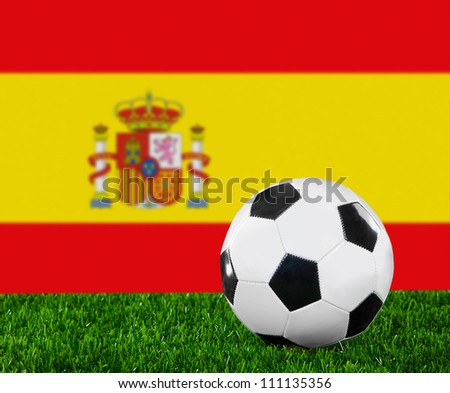 The Spanish flag and soccer ball on the green grass