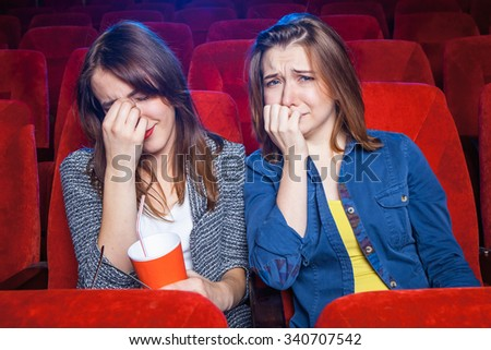 The spectators sitting in the cinema and watching movie  with cups of popcorn. Concept of a variety of human emotions.