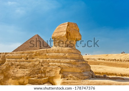 The Sphinx with Pyramid in background, Egypt Cairo - stock photo