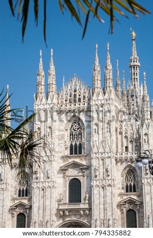 The splendid facade of the gothic cathedral of Milan framed by some branches of palm trees, Lombardy, Italy