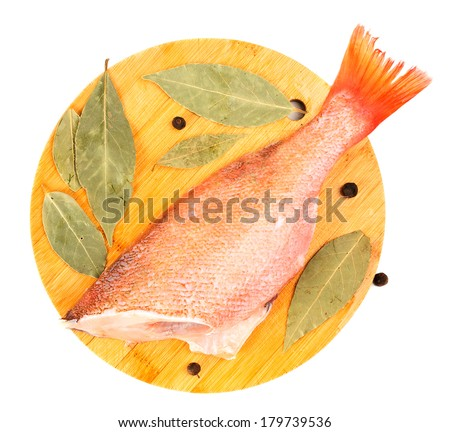 The split sea bass on a round cutting board. - stock photo