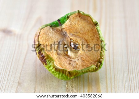 the spoiled cut green apple on a wooden board - stock photo