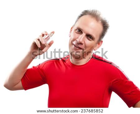 The sports man spraying fragrance perfume  - stock photo