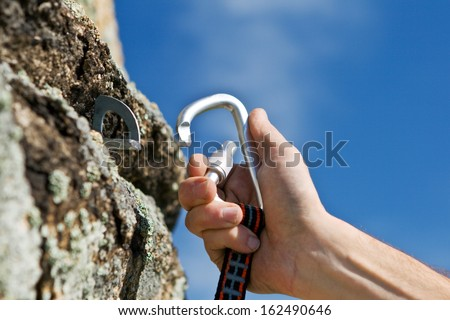 The sportsman hangs up carbine in hook on background blue sky - stock photo