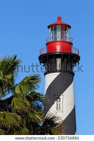 The St. Augustine Lighthouse, with it's distinctive black and white spiral topped with a red lantern room, towers above the palms of Florida's Atlantic Coast. - stock photo