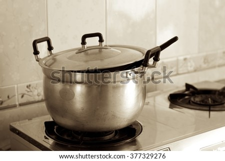 The stainless pot on gas stove; Sepia color - stock photo
