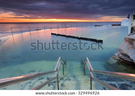 The stairs leading down into  Bronte rock pool, Sydney as the dawn light colours the sky.  The pool is built on the rockshellf and nestles into the rising cliff face e southern end of beach. - stock photo