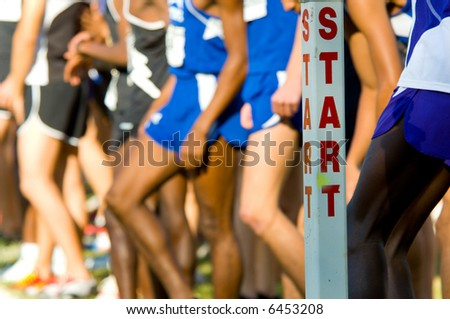 The start line at the beginning of a cross country race with runners in the background - stock photo