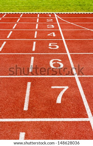 The starting lines at stadium, white lines and numbers on the track .