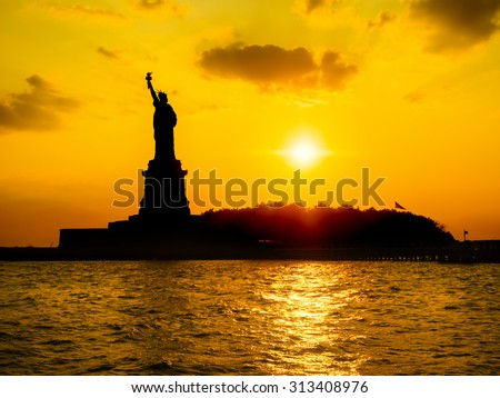 The Statue of Liberty at sunset with reflections on the ocean - stock photo