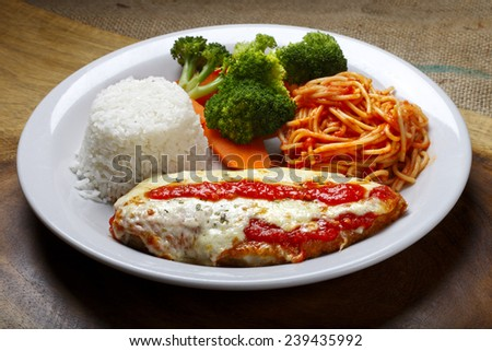The steak parmigiana with pasta and rice - stock photo
