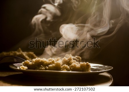The steam from the cooling porridge on the table. Vegetarian lunch or breakfast. Clouds of steam over the dish. porridge in a plate. Oatmeal for breakfast.  steam over the plate - stock photo