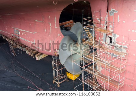 The stern of the container ship on dry dock. Propeller and rudder maintenance.