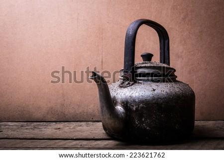 the still life old aluminium kettle on the wooden background - stock photo