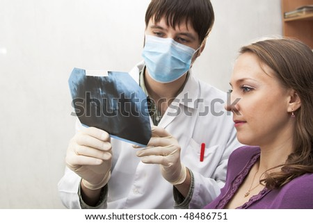 The stomatologist shows x-ray picture