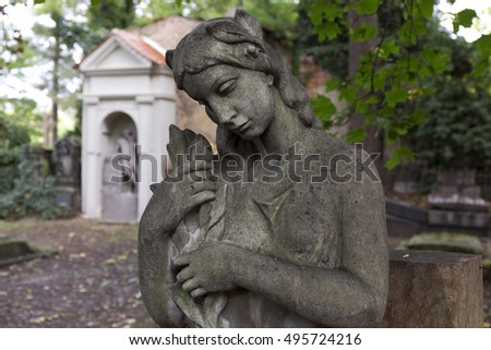 The stone Girl on Tomb from the autumn old Prague Cemetery, Czech Republic