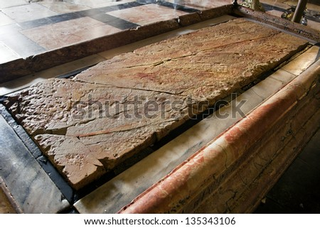 The stone of the Anointing at the Church of the Holy Sepulchre in the old city of Jerusalem, Israel. Also known as 'The Stone of Unction', is the spot where Jesus' body was prepared for burial. - stock photo