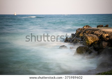 The stones in the foreground, the frozen water effect, in the distance the lighthouse on the horizon/ The lighthouse in the distance/ Seascape - stock photo