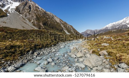 The stones river at Hooker Valley to Mount Cook, New Zealand with  snow capped mountains view, brown tussock grass and blue sky