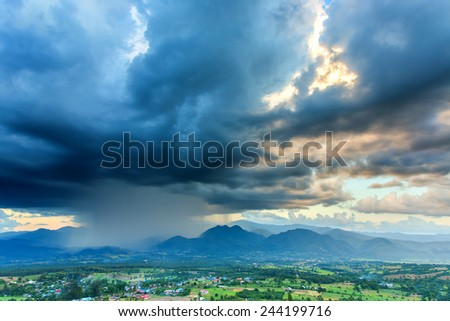 The storm was brewing in the mountains near the city. - stock photo