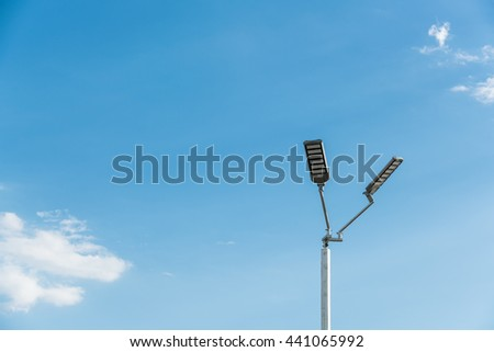The street light pole with a blue sky background - Automatic street twin lamp against the blue sky with copy space  - stock photo