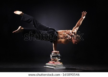 The strong man is standing on the books - stock photo