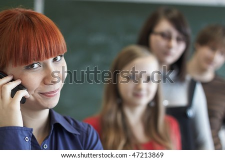 The student speaks by phone in a class room - stock photo