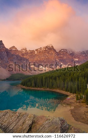 The stunning Moraine Lake as the sunrise colours make a brief appearance - stock photo