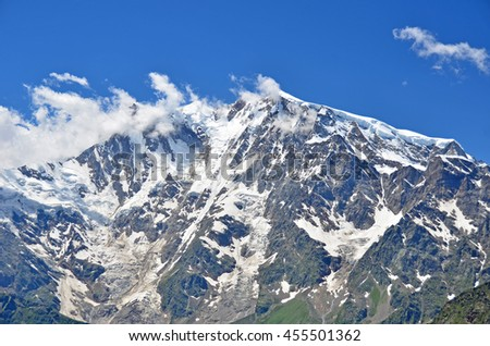 The summits of Monte Rosa in the Italian Alps with small fair weather clouds clinging to the tops in the summer. The highest mountain in Italy - stock photo