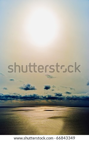 The sun before sunset against black storm clouds over the sea - stock photo