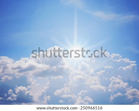 the sun breaking through a cluster of clouds a sun flare on a sunny day with blue sky - stock photo