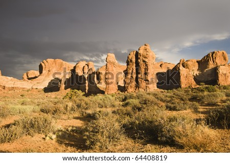 The sun breaks out over Arches National Park after a rainstorm passes over. Dark clouds in the background. - stock photo