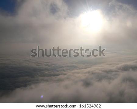 The sun glows through fog over dense clouds. - stock photo