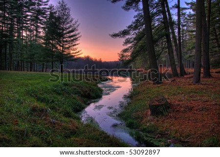 The sun goes down at a remote forest lake. - stock photo