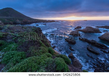 The sun goes down over the Pacific in Big Sur, California - stock photo