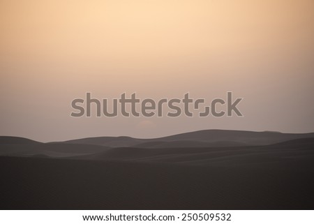 The  sun has fallen behind the horizon. A reddish sky in the Sahara desert in Morocco, with dunes in the front. - stock photo