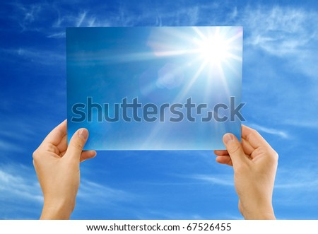 The sun image in hands against the sky - stock photo