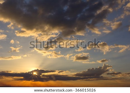 The sun is going down and the sky with clouds lot. - stock photo
