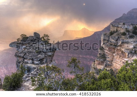 The sun lights up the low clouds and swirling snow seen from Mather Point in Grand Canyon National Park, Arizona. - stock photo