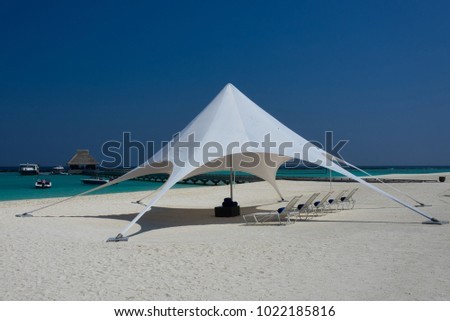 The sun loungers under the big sun shade on the idyllic beach. Maldives private islands