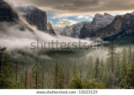 The sun peaks over the Sierras for its first glimpse of the Yosemite Valley. - stock photo
